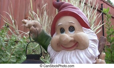 Sculpture of dwarf with lamp in hands in garden. From top to...