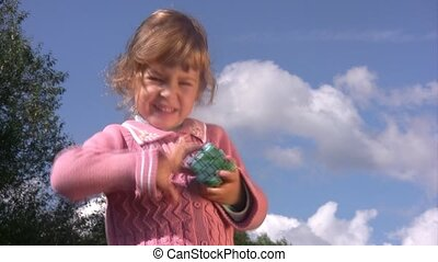 Little girl solves puzzle cube with earth pattern. - Little...