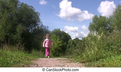 Little girl skip back on path in park Summer sunny day