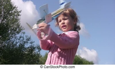 Little girl plays with toy plane and launch it.