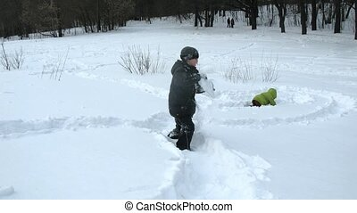 Kids play in snow digging tunnels, time lapse - Two little...