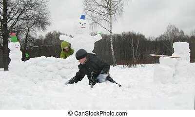 Kids play in snow sculpting snowman, time lapse