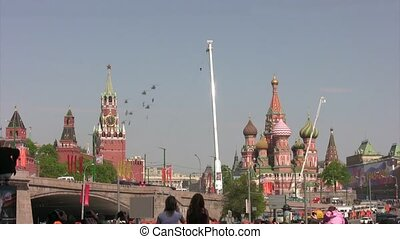 Group of helicopters fly with flags over Red Square.