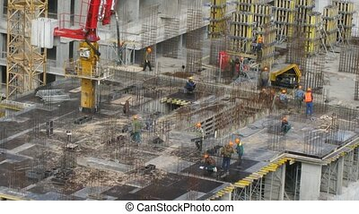 Don-stroy workers place rebars at top of building at Losiniy...