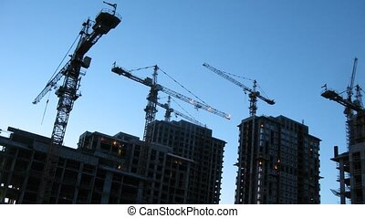 Crane silhouettes at construction site in evening, time lapse