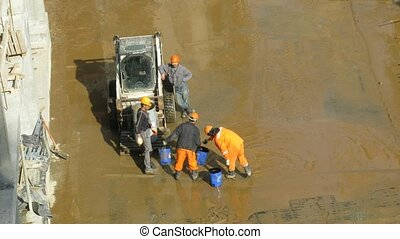 Workers dip out water on construction site at Losiniy Ostrov...