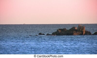 Rocks in water, boat in the distance. - Rocks in water, a...