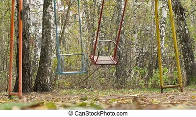 Two swings swaying in park - Two swings colored in different...