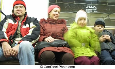 Family in subway train, time lapse - Family wearing warm...