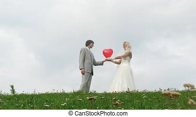 Newlywed pair poses with heart balloon in front of cloudy sky