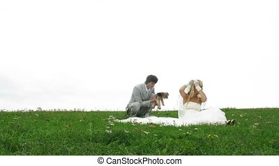 Photographer shoots newlywed pair with little doggie