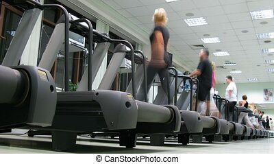 People on treadmills at fitness club. Machine provides a...