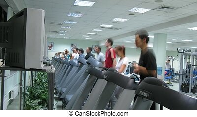 People watch TV on treadmills at Multisport fitness club -...