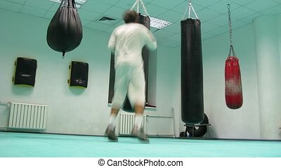 Man dressed in white hit four different punchbags, time...