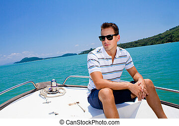Man Relaxing On A Boat - An attractive young man relaxing...