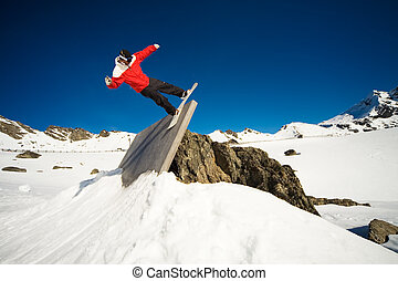 Snowboard wall ride - Snowboarder doing trick on wall ride,...