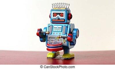 Closeup of clockwork robot make steps on table