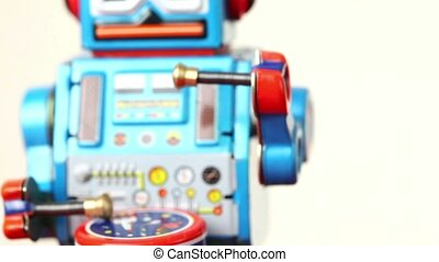 Closeup of clockwork robot walks on table, beats drum