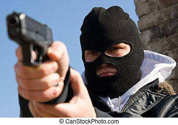 Criminal in mask aiming his target - Armed criminal man...