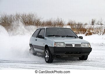 Drift of a grey sport car over snow