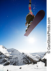 Airborn snowboarder - Snowboarder jumping through air with...