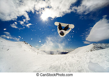 Snowboarder backflip - Snowboarder going off jump doing a...