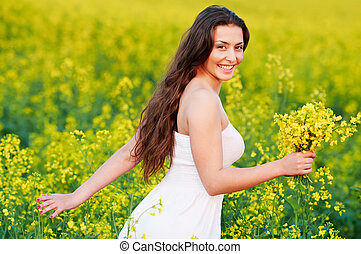 girl with flowers at summer field