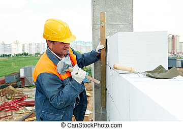 construction mason worker bricklayer installing calcium...