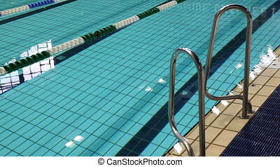 swimming pool with blue water, and rail at its edge -...