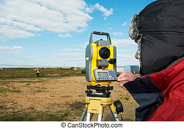 surveyor works with theodolite tacheometer - Surveyor worker...