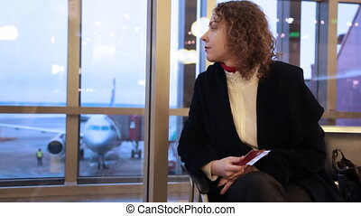 Woman sitting by window airport with documents in hand