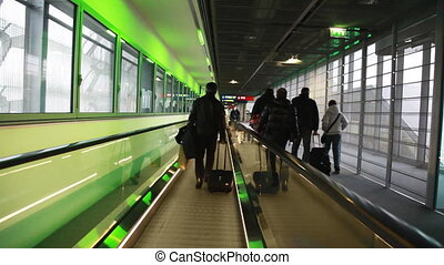 People go to corridor horizontally moving escalator at exit...