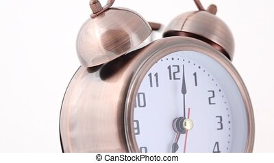 close-up shot of rotating and ringing alarm clock on white