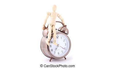 wooden doll sitting on ringing alarm clock, rotating on...