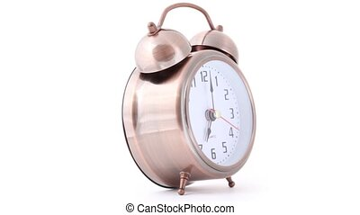 rotating and ringing classical alarm clock on white