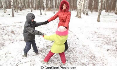 Mother with children are turned in wood. - Happy mother with...