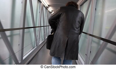 Man walks along narrow corridor with glass walls - man walks...