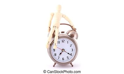 wooden doll sitting on ringing alarm clock, white background