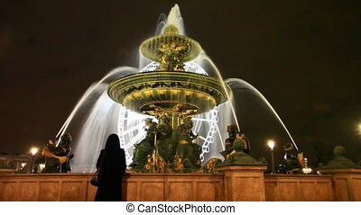 Woman at lighted fountain des Mers