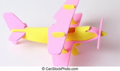 airplane yellow and pink toy rotating on white