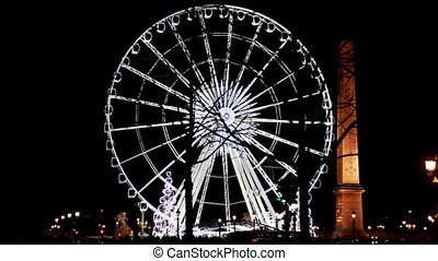 Lighted Ferris wheel and Luxor obelisk at Champs Elysees...