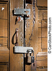 Padlock on weathered brown door