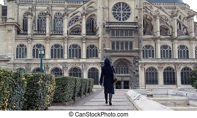 Woman goes on square to ancient cathedral