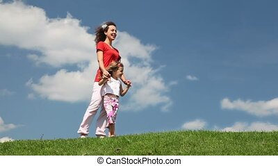 Mother and daughter standing on meadow holding hands in...
