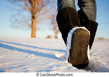 Walking in the Snow - Close up of a woman\'s boots walking...