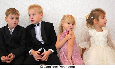 Four children in celebratory clothes sit in room - Four...