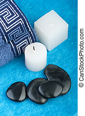blue spa setting with hotstones, candles and towels