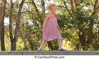 Smiling little girl goes on stone border