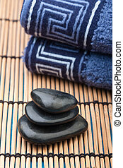 oriental hotstone treatment - pile of hotstones with blue...