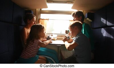 Family drinks tea in train - Family with two children drinks...
